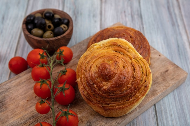 Top view of buns on a wooden kitchen board with fresh vine tomatoes with olives on a wooden bowl on a grey wooden background