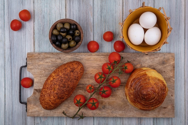 Top view of buns on a wooden kitchen board with vine tomatoes with olives and eggs on a grey wooden background