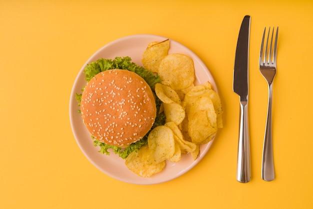 Вид сверху бургер и чипсы со столовыми приборами