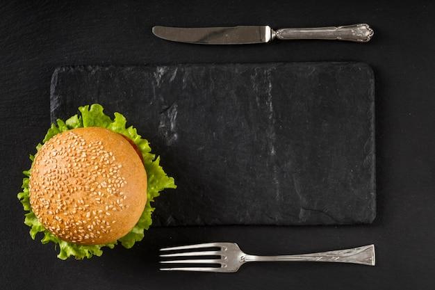 Гамбургер и столовые приборы вид сверху