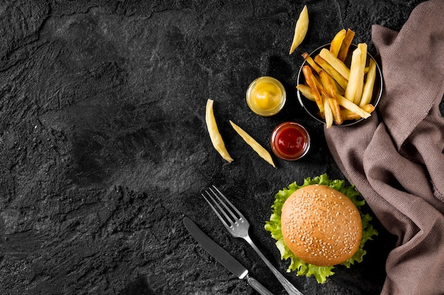 Гамбургер и картофель-фри с соусами и копировальным пространством, вид сверху