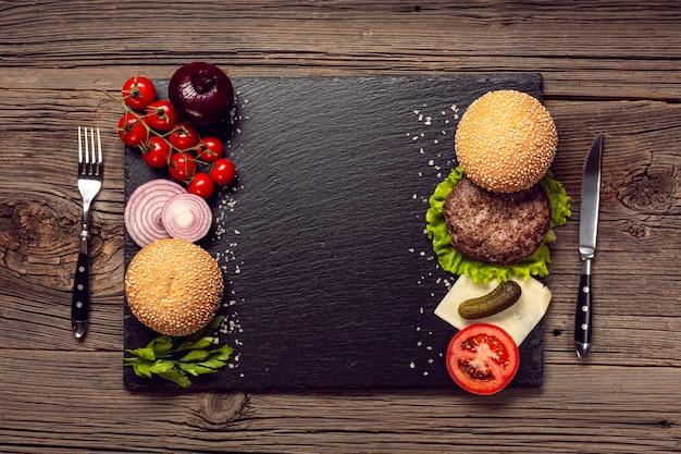 Top view burger ingredients on a black boardon