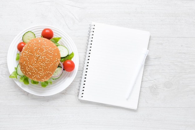 Top view burger for vegans next to empty notebook