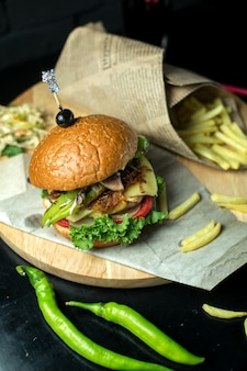 Top view burger with french fries and green pepper on blackboard