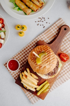 Top view of burger with french fries on a wooden board