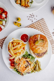 Top view of burger with vegetable salad and french fries