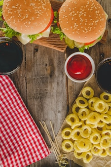Top view of burgers, onion rings and tablecloth