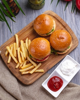 Top view burgers with french fries ketchup with mayonnaise and tomatoes