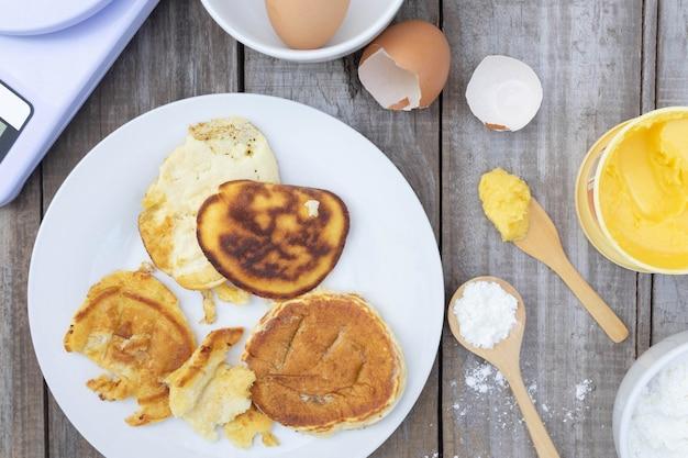 상위 뷰, 나무 배경에서 하얀 접시에 탄된 팬케이크, 음식 개념을 먹을 수 없습니다.