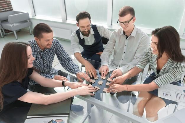 Вид сверху. коллеги по бизнесу собирают пазл, сидя за столом. бизнес-концепция