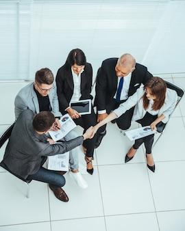평면도. 사무실 회의에서 악수하는 사업 동료. 공간의 사본이있는 사진