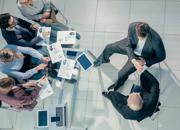 上面図。お互いに握手するビジネスの同僚。協力の概念。