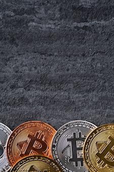 ダークブラックのスレートテーブルの背景にビットコイン暗号通貨のお金のトップビュービジネスコンセプト。