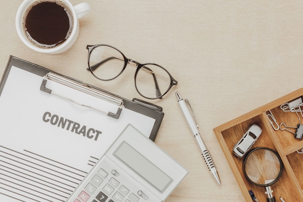 Top view business contract form with coffee eyeglasses car calculator pen with magnifying glass on wooden background.