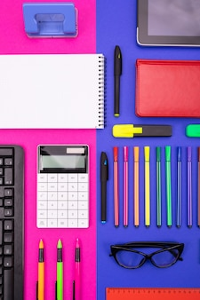 Top view of business desk composite with smartphone, calculator, stickers, and colored pens on pink and blue