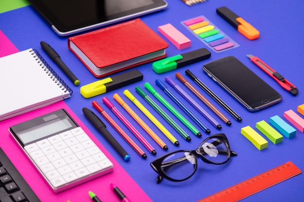 Top view of business desk composite with smartphone, calculator, stickers, and pens on colorful pink and blue