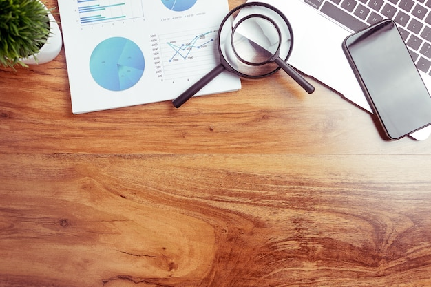 トップビュー、ノートブック付きビジネスデスク、レポートグラフチャート、ペン、タブレット、木製テーブル