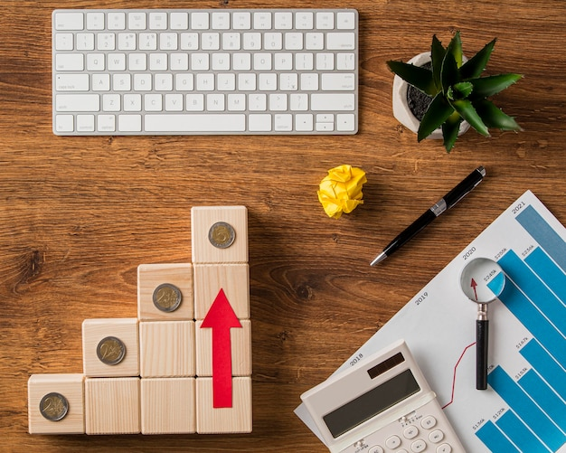Top view of business items and arrow pointing up with wooden blocks