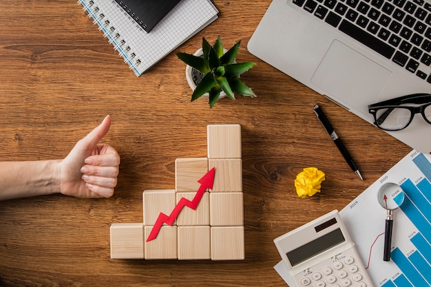 Top view of business items and growth arrow with hand giving thumbs up