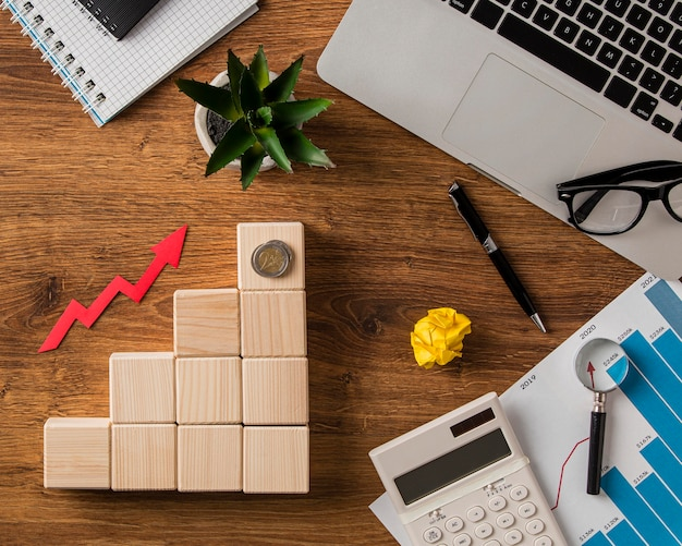 Top view of business items and growth arrow with wooden blocks