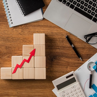 Top view of business items and growth arrow on wooden blocks