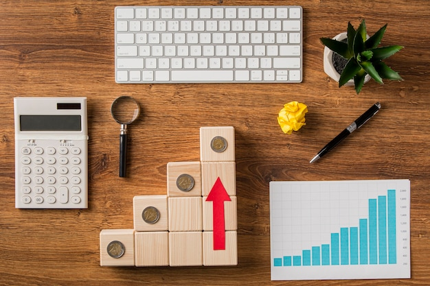 Top view of business items with arrow on wooden blocks pointing up