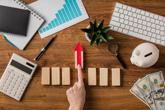 Top view of business items with growth chart and hand pushing up wooden block