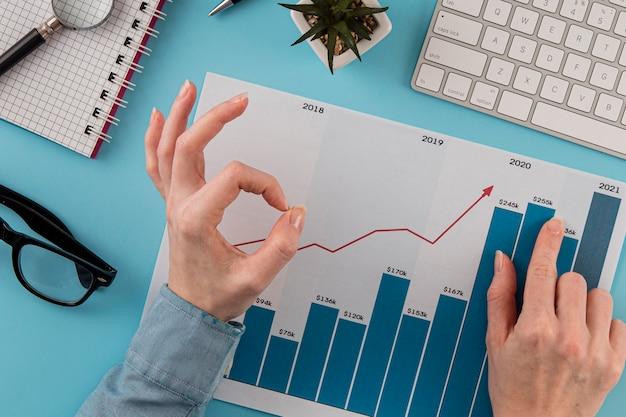 Vista dall'alto di elementi aziendali con grafico di crescita e mani che danno segno giusto