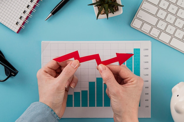 Top view of business items with growth chart and hands holding arrow