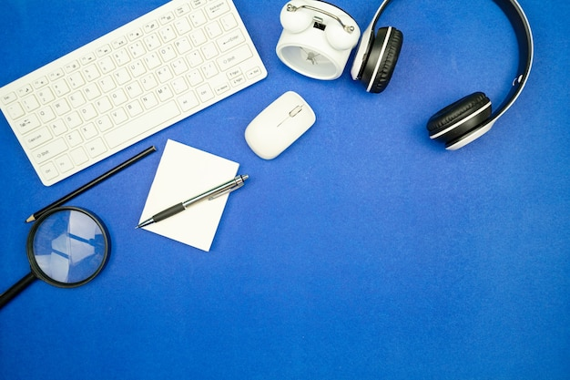 Top view of business objects keyboard,mouse,headphone,paperwork with pencil and alarm clock on blue paper background minimal flat lay copy space for business background and website.