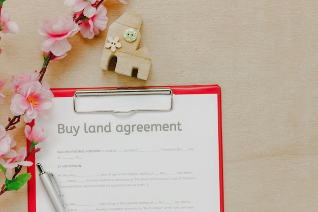 Top view business office desk background.the business buy land ageement form pencil wood house beautiful pink flower on wooden table background with copy space.