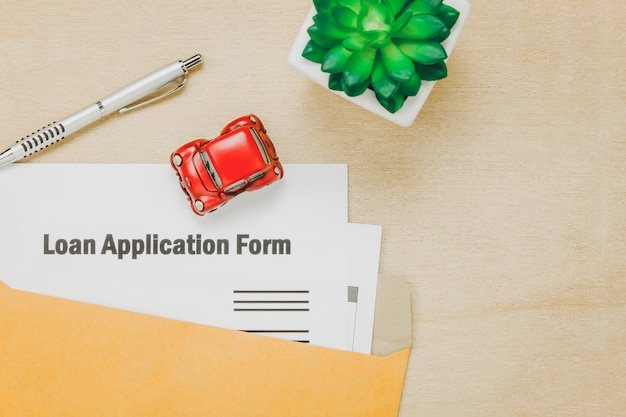 Top view business office desk background.the business loan appcation form pencil  letter and car tree on wooden table background with copy space.