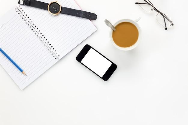 Вид сверху бизнес-офис desk.mobile телефон, очки, часы, кофе, ноутбук, карандаш на белом офисный стол с копией пространства.