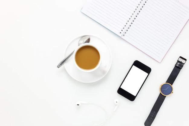 Вид сверху рабочий стол office.mobile phone, часы, кофе, notebookl на белом офисный стол с копией пространства.