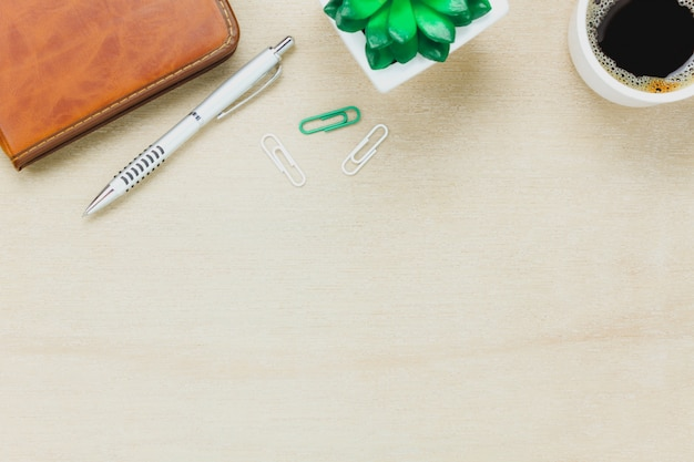 Top view business office desk.the notebook,pencil,black coffee,tree,paperclips on wooden table background.