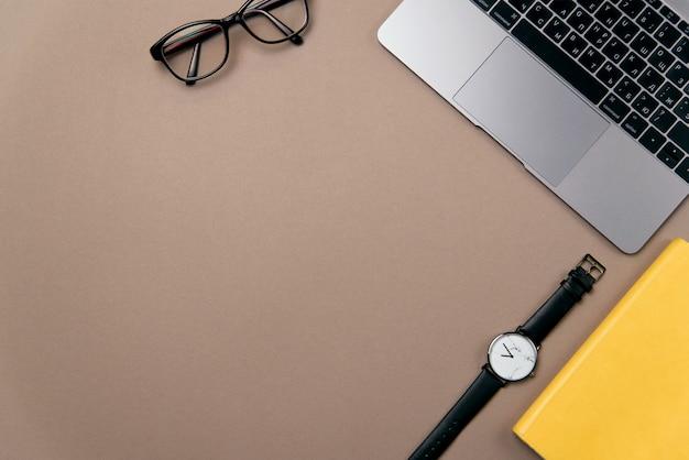 상위 뷰 비즈니스 사무 용품. 노트북, 노란색 노트북, 안경 및 갈색 사무실 책상 배경에 시계.