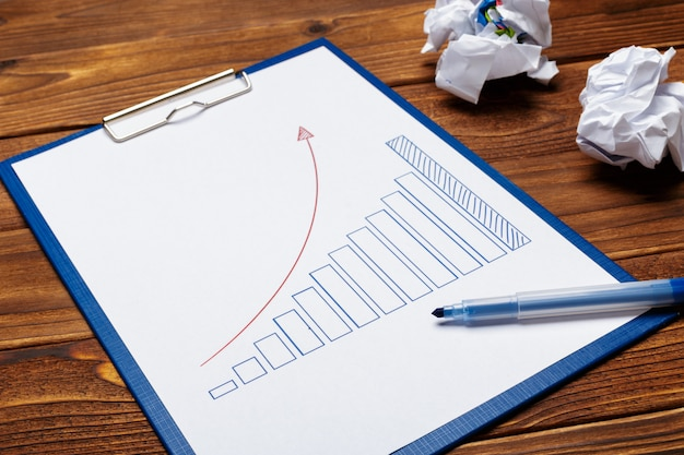 Top view of business paper chart or graph on wooden table