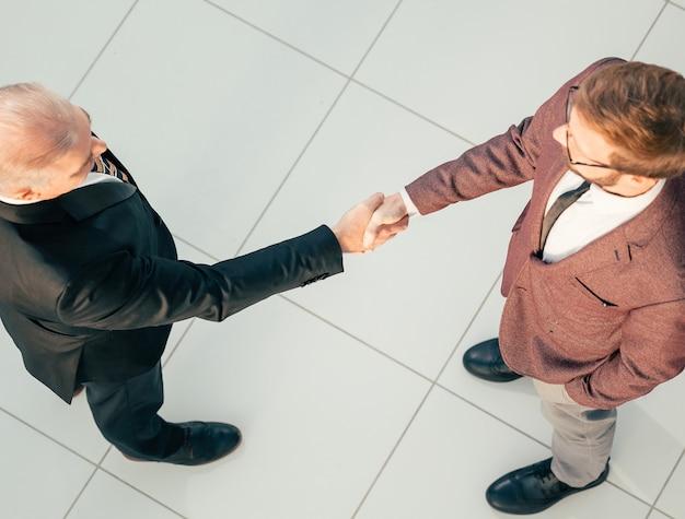 Вид сверху. деловые партнеры, подтверждающие транзакцию рукопожатием