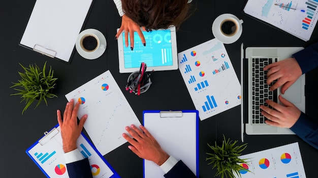 Top view of business people having meeting analysing financial statistics graphs planning next project using digital devices on corporate office