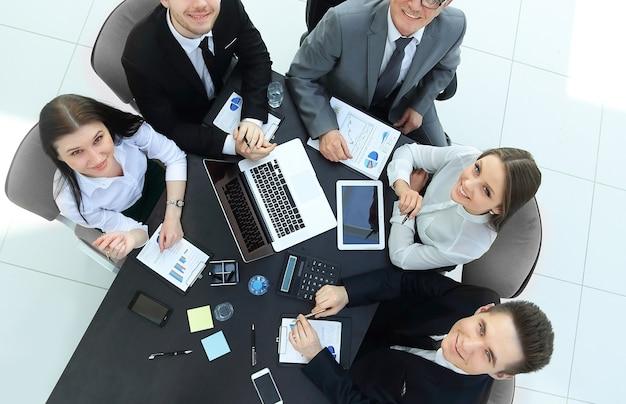 トップビュー。カメラを見ているデスクのビジネスチーム。チームワークの概念