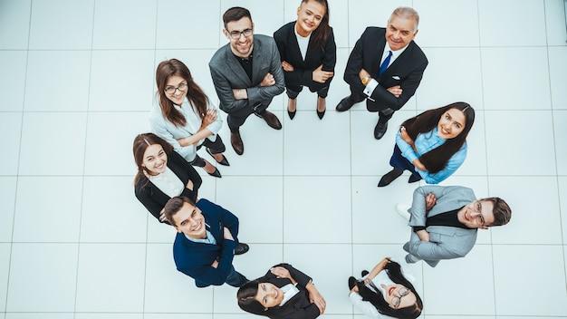 평면도. 원 안에 서 있고 카메라를보고 비즈니스 팀. 공간의 사본이있는 사진