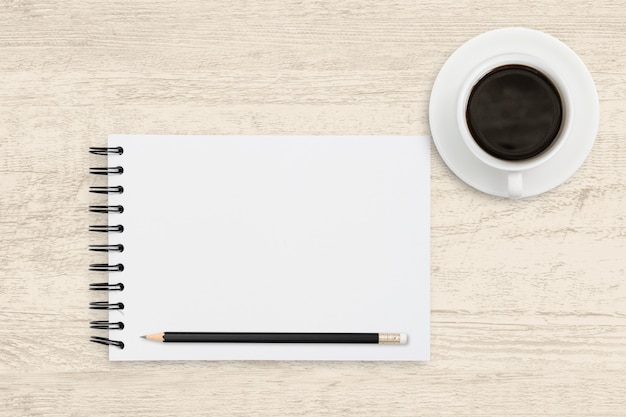 Top view business of white paper sheet of notebook with coffee cup on wood background.