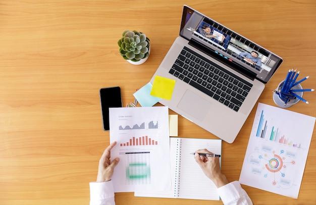 Вид сверху бизнесмен и бизнес-леди анализ финансовой диаграммы с видеоконференцией онлайн-встречи.