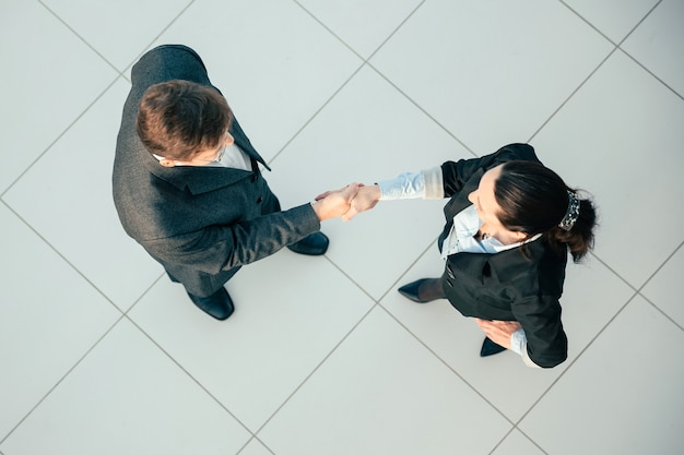 Вид сверху. бизнесмен и бизнесвумен, пожимая друг другу руки