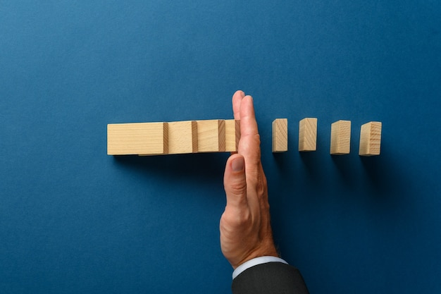 Top view of businessman hand interfering to stop collapsing dominos