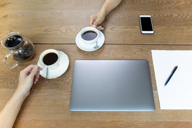 Top view of businessman hands holding coffee cup with laptop on table.