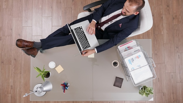 Top view of businessman keeping his feet on desk while typing management statistics