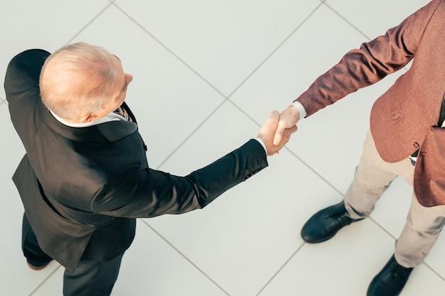 上面図。彼のビジネスパートナーと握手するビジネスマン