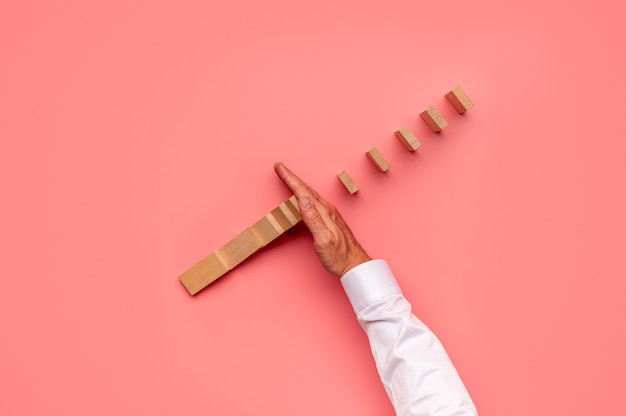Top view of businessman stopping falling dominos with his hand. over pink background.