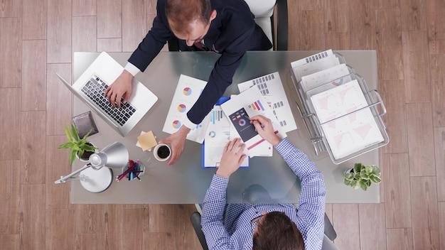 Vista dall'alto dell'uomo d'affari in tuta che beve caffè durante la riunione di collaborazione
